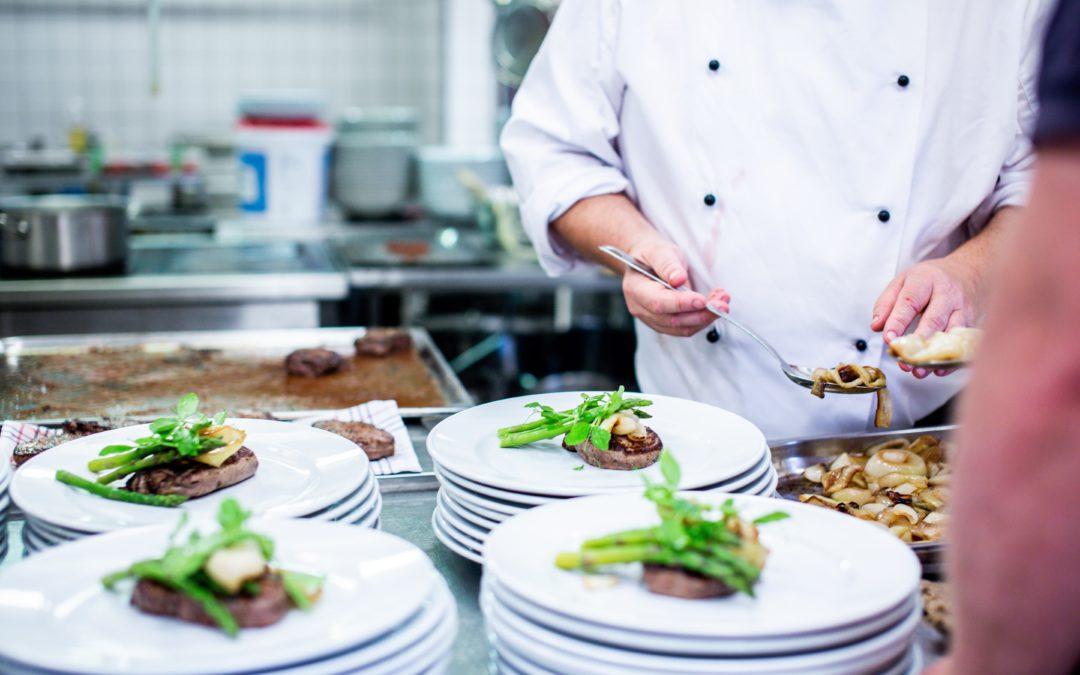 Kok in keuken die voedsel klaarmaakt