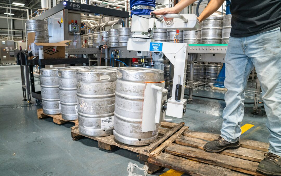 man-operating-silver-machine-for-silver-steel-kegs-Handgel gemaakt van oud bier